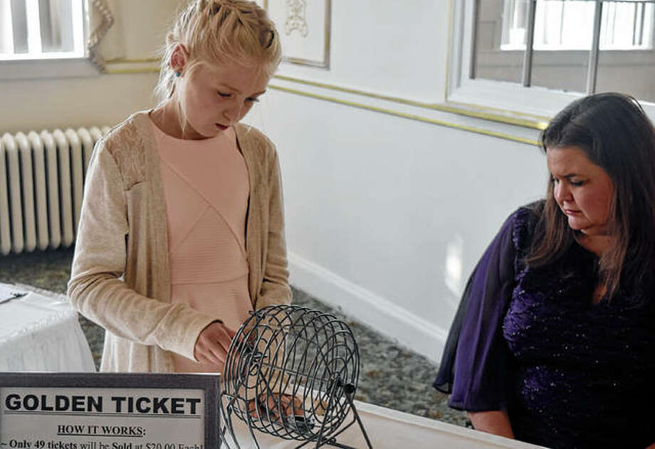 McKenzie Jones, the daughter of Shianna Still, helps place a numbered ball into a wire cage Friday during the Kourtnee's Chiari Care Connection's fundraiser. Each ball corresponded with the number on a Golden Ticket that was randomly drawn during the event.