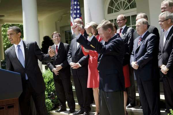 President Barack Obama gestures toward Alan Mulally, then CEO of Ford, at the White House on May 19, 2009.