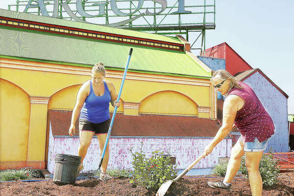 Michelle Wolff, right, and her daughter, Meghan, from 4-M Landscaping in Bunker Hill, work Thursday to replace and mulch new shrubs and other plants that were washed away from the Argosy Casino Alton this summer by the second worst flood in recorded history. Re-landscaping the outside of the Alton casino is just one of things being done as the business bounces back after the flood.