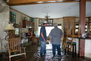 Cousins Richie Devillier, 56, left, and Steve Devillier, 59, look around Steve's flooded house on Devillier Road  on Friday, Sept. 20, 2019, in Winnie. While water has started to go down on the south side of the Interstate Highway 10, the north side of the highway was still under deep water.
