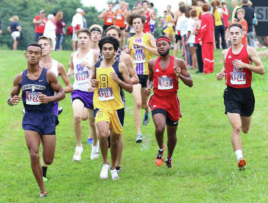 Alton's Cassius Havis (second right) runs on the lead with Father McGivney's Tyler Guthrie (1224), John Burroughs' Akash Mallady (1318) and Highland's Nick Hanratty (right) in the second mile of the Edwardsville Invitational boys cross country race Saturday morning at SIUE in Edwardsville. Photo: Greg Shashack / The Telegraph