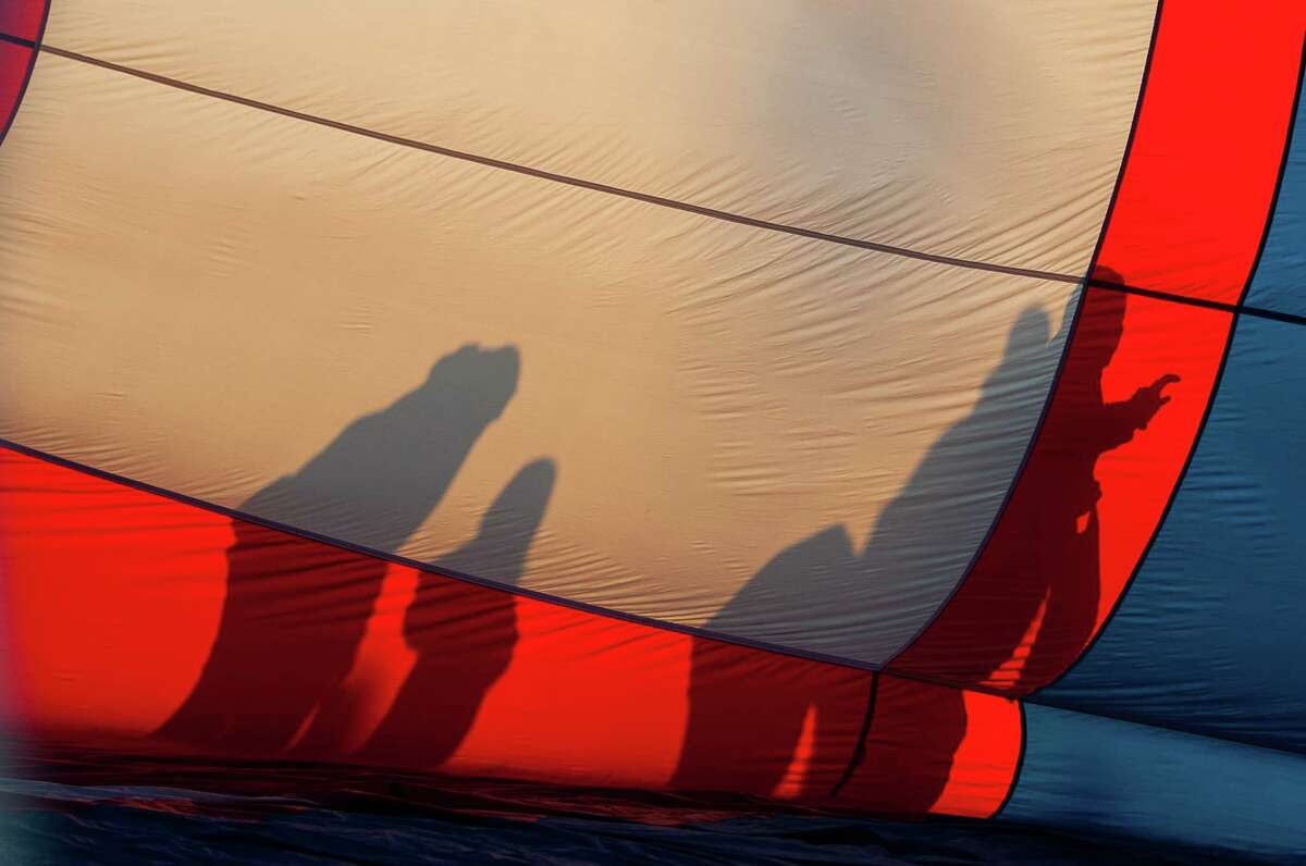 Silhouettes appear on the side of a hot air balloon being inflated at the Saturday morning launch of the 47th Annual Adirondack Balloon Festival on Sept. 21, 2019, in Queensbury, N.Y. (Jenn March, Special to the Times Union )