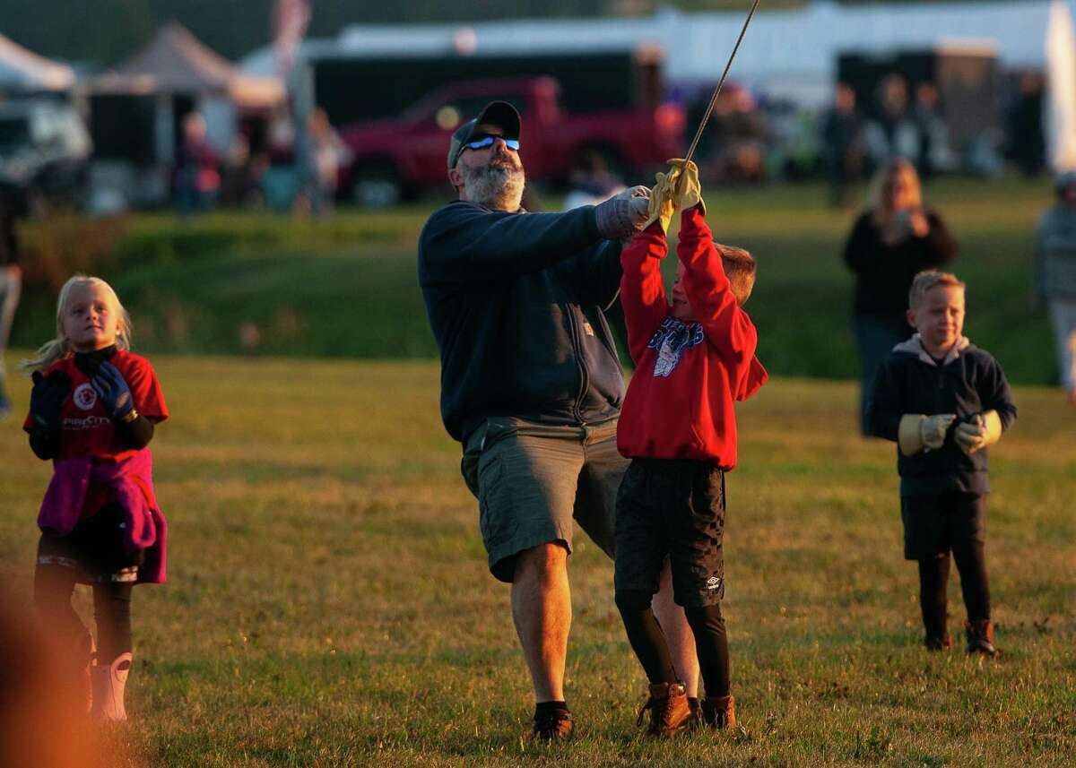 Brody Smith is lifted slightly from the ground as he helps his uncle, Ben Smith of South Glens Falls hold the tether for a balloon piloted by Alan Jones of Pennsylvania during the morning launch Saturday, Sept. 21, 2019, of the 47th Annual Adirondack Balloon Festival at Floyd Bennett Memorial Airport in Queensbury, N.Y. (Jenn March, Special to the Times Union )