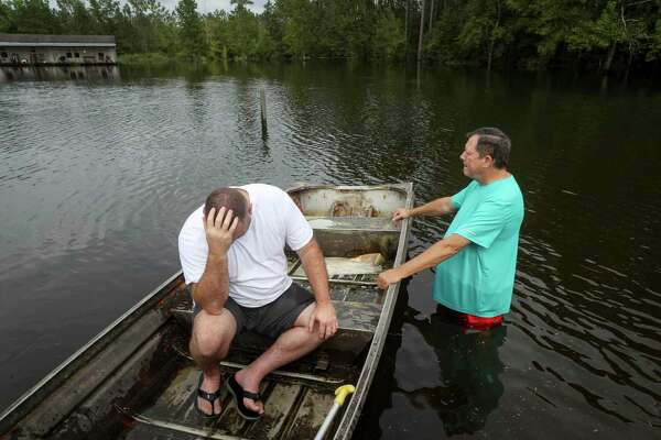 """Stephen Gilbert, left, and his father-in-law sit in front of their flooded property on Friday, Sept. 20, 2019, in the Mauriceville area. """"I'm on my third house,"""" said Gilbert, who lives behind his father-in-law. """"I wouldn't go anywhere else in the world,"""" he said. """"All we have is family anyway."""""""