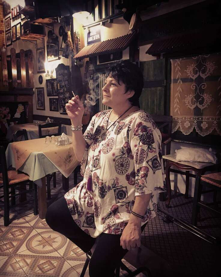 Maria Pavlopoulou smokes near the stage where she sometimes sings in Athens on Sept. 17, 2019. Photo: Photo For The Washington Post By Loulou D'Aki / The Washington Post