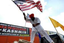 Gagandeep Singh puts American flags on a pickup truck as he and others prepared for a truck rally at the Sikh National Center Gurdwara, Saturday, Sept. 14, 2019, in Houston. The rally is organized by the national human rights organization Sikhs for Justice and Friends of Kashmir, comprising of Kashmiri and Sikh people who are protesting Prime Minister Modi and his forthcoming appearance on Sunday September 22nd at NSG stadium, where 30,000 demonstrators are expected to protest India's actions in Kashmir and Punjab.