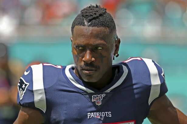 In this Sunday, Sept. 15, 2019, photo, New England Patriots wide receiver Antonio Brown waits for the team's NFL football game against the Miami Dolphins to begin in Miami Gardens, Fla. \Brown was released by the Patriots on Friday, Sept. 20, after a second woman accused him of sexual misconduct. (David Santiago/Miami Herald via AP)
