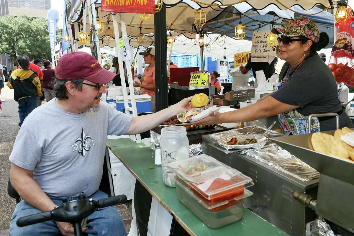 Bill Woodland puts mustard on a sausage shish-ka-bob sold by Leonor Rios at the Gorditas booth at the 36th Annual Jazz'SAlive festival at Travis Park on Saturday, Sept. 21, 2019. This year's festival featured five-time Grammy winner Diane Reeves and local acts including The Lao Tizer Band, The U.S. Air Force Band dimensions in Blue and the Adrian Ruiz Quartet