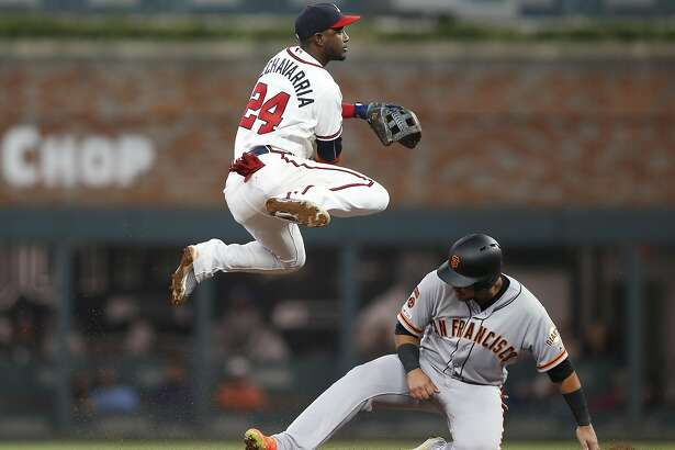 ATLANTA, GEORGIA - SEPTEMBER 21: Second baseman Adeiny Hechavarria #24 of the Atlanta Braves turns a double play over second baseman Cristhian Adames #14 of the San Francisco Giants in the fifth inning during the game at SunTrust Park on September 21, 2019 in Atlanta, Georgia. (Photo by Mike Zarrilli/Getty Images)