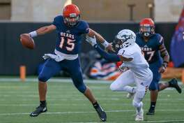 Bridgeland quarterback Conner Weigman (15) evades a tackle by Cypress Ranch defensive back Robin Neely (7) in the first quarter of a high school football game, Saturday, Sept. 21, 2019 in Cypress, TX.
