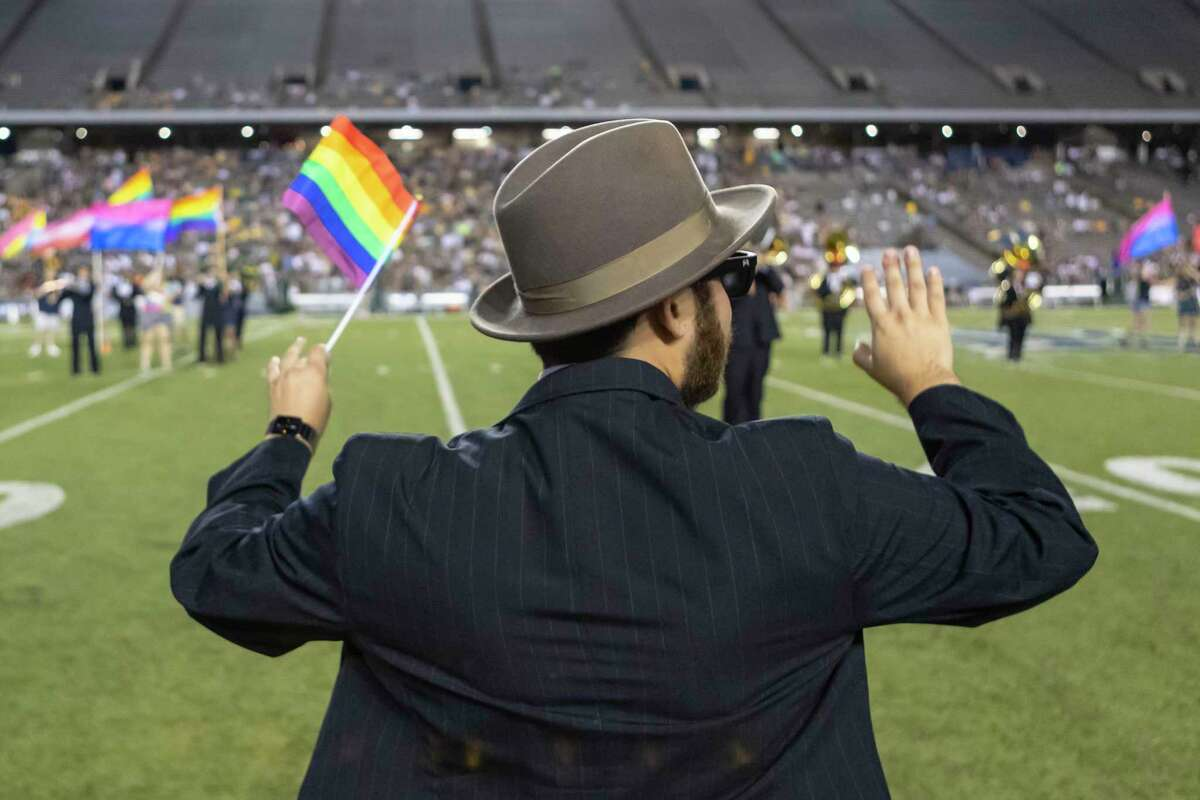 Rice student supporting the LGBTQ community run onto the field to perform with the Rice marching band during half time of a college football game Saturday, Sep 21, 2019, in Houston.
