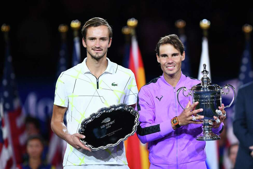 TOPSHOT - Rafael Nadal of Spain (R) holds the trophy after his win over Daniil Medvedev of Russia (L) during the men's Singles Finals match at the 2019 US Open at the USTA Billie Jean King National Tennis Center in New York on September 8, 2019. - Rafael Nadal captured his 19th career Grand Slam title in thrilling fashion on Sunday by winning the US Open final, outlasting Russia's Daniil Medvedev 7-5, 6-3, 5-7, 4-6, 6-4 to seize his fourth crown in New York. (Photo by Johannes EISELE / AFP)JOHANNES EISELE/AFP/Getty Images