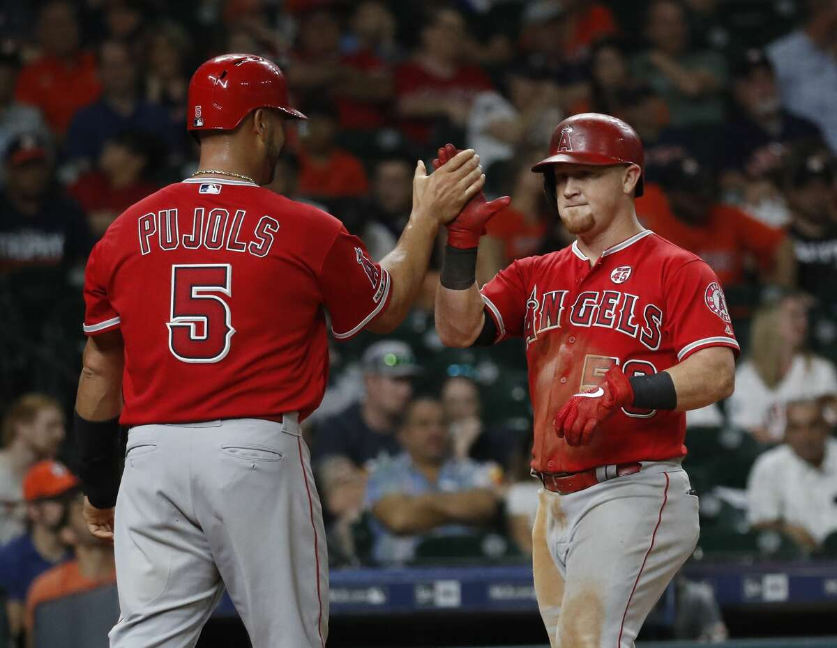 Los Angeles Angels Kole Calhoun (56) celebrates his two-run home run with Albert Pujols (5) in the ninth inning of an MLB baseball game at Minute Maid Park, Saturday, Sept. 21, 2019, in Houston.