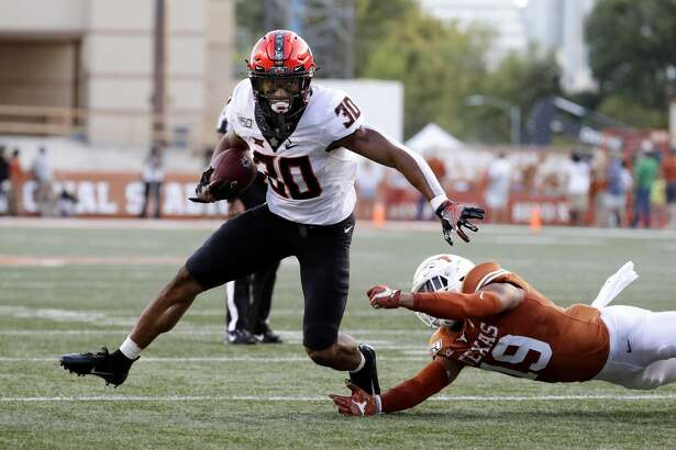 Oklahoma State running back Chuba Hubbard (30) runs past Texas defensive back Brandon Jones (19) during the first half of an NCAA college football game Saturday, Sept. 21, 2019, in Austin, Texas. (AP Photo/Eric Gay)