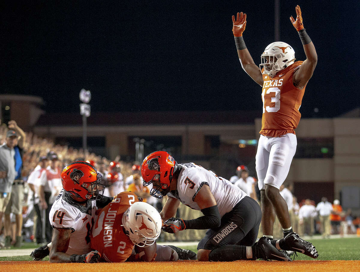 Texas running back Roschon Johnson (2) scores a two-point conversion against Oklahoma State during an NCAA college football game Saturday, Sept. 21, 2019, in Austin, Texas. (Nick Wagner/Austin American-Statesman via AP)