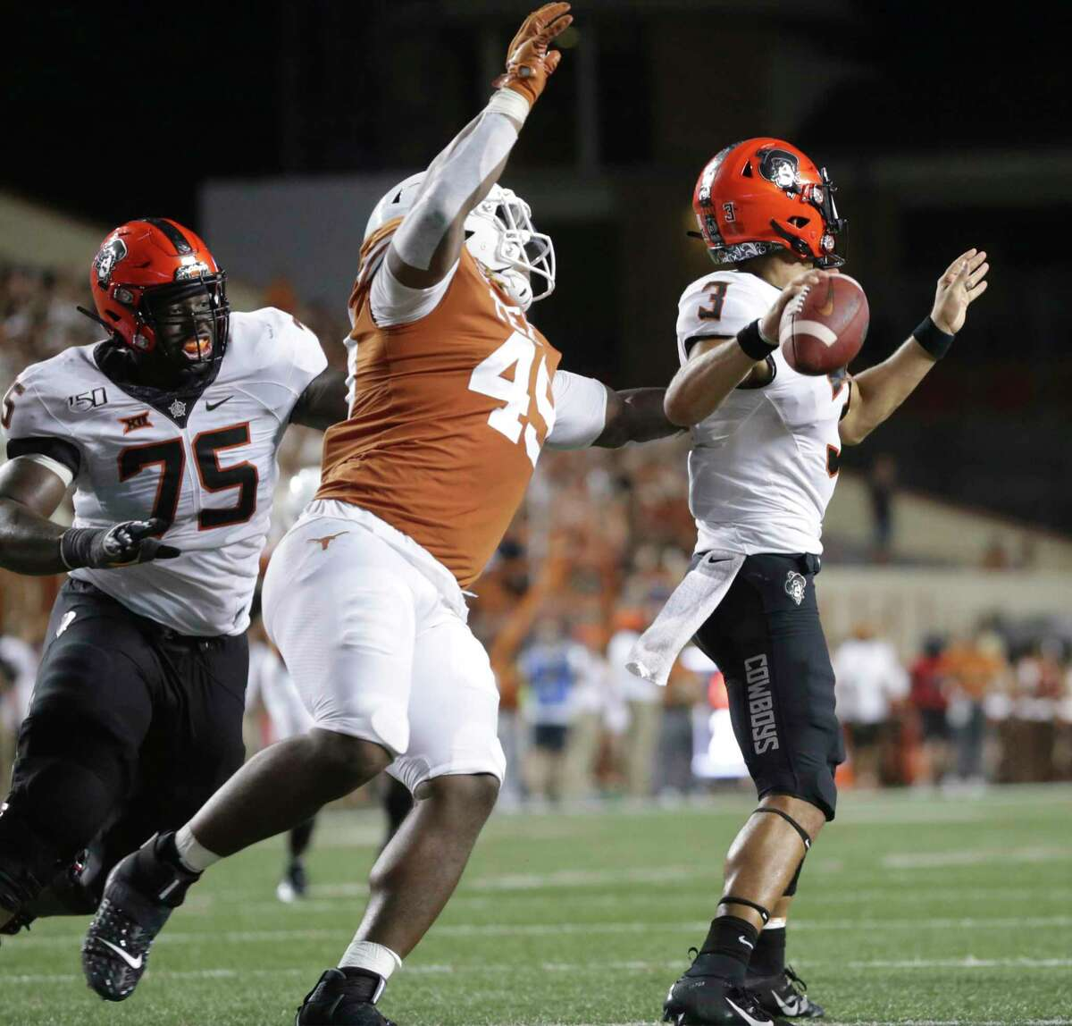 Horn's defensive linemane Ta'Quon Graham gets around the back side of Cowboys quarterback Spencer Sanders to deflect his pass as Texas hosts Oklahoma State University at DKR Royal Stadium in Austin on Sept. 21, 2019.