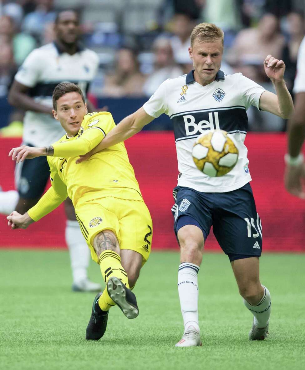 Columbus Crew's Luis Argudo, left, takes a shot on goal as Vancouver Whitecaps' Andy Rose defends during the second half of an MLS soccer match in Vancouver, British Columbia, Saturday, Sept. 21, 2019. (Darryl Dyck/The Canadian Press via AP)