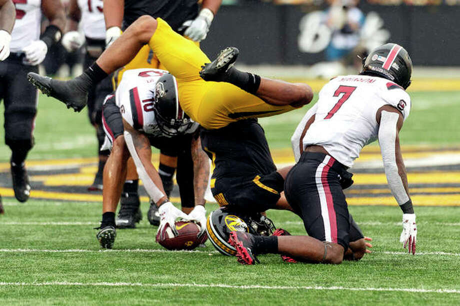Missouri quarterback Kelly Bryant, center, loses the ball after hitting the ground between South Carolina defensive back Jammie Robinson, right, defensive back R.J. Roderick, left, during Friday's game in Columbia, Mo. Photo: AP Photo