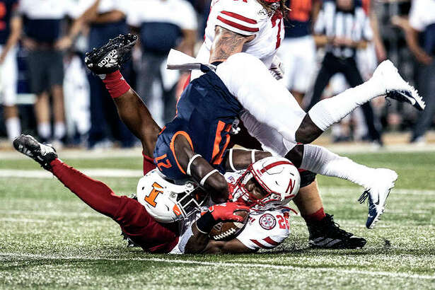 Nebraska's Dedrick Mills (26) is brought down by Illinois' Jartavius Martin (21) Saturday night in Champaign.