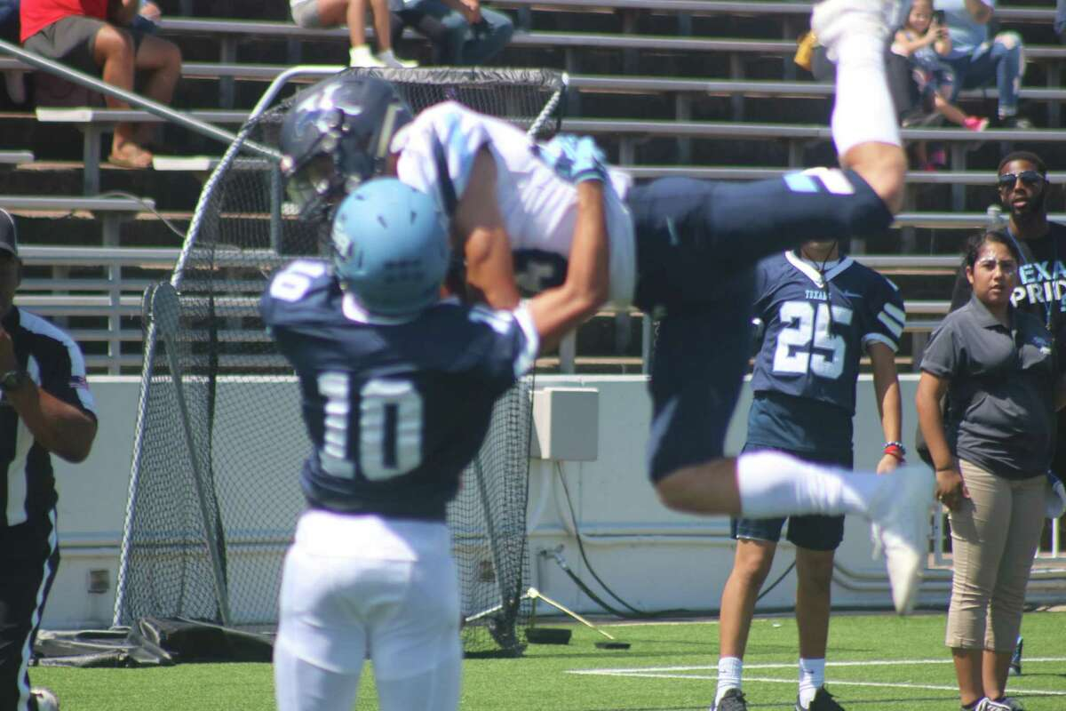Kingwood quarterback Grant Wall flies through the air at the end of a 10-yard run that got his teammates close to the end zone. Wall had a hand in five Mustang TDs Saturday afternoon. Elijah  Garcia is the defender.
