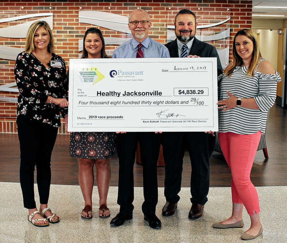 Kevin Eckhoff (center), Passavant Area Hospital communications director and director of the 2019 Passavant-Gatorade 5K/10K Race, presents a check for $4,800 to Healthy Jacksonville representatives Sarah Karraker (from left), MSW, LCSW; Andrea Phelps; Dr. Scott Boston, Passavant president and CEO; and Erika Jennings. The funds represent proceeds from the race and will benefit clients of Healthy Jacksonville, a collaborative effort spearheaded by Passavant to improve access to health care for at-risk Jacksonville residents. Healthy Jacksonville used a portion of the proceeds to send youth from Jacksonville's northeast side to Western Illinois Youth Camp earlier this summer. The remainder will be used for the future restoration of Minnie Barr Park. Photo: Photo Provided