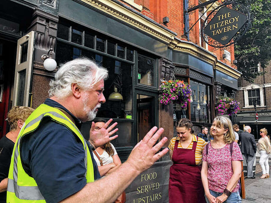 Writer and tour guide Nick Hennegan leads a group of tourists through London's Fitzrovia area in July to explore pubs connected to famous writers. The London Literary Pub Crawl allows visitors to experience a playful and IPA-fueled tour unlocks stories linked to London locations where renowned novelists and poets drank and debated literature. Photo: Russell Contreras | Associated Press