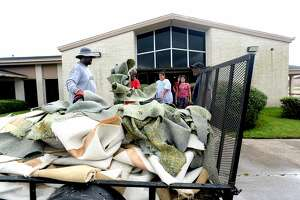 Members of Cathedral of Faith Church on Fannett Road remove dampened carpeting from the sanctuary, which had about a foot of flood water, as the process of recovery from Imelda's torrential rains and flooding begins throughout the region Friday. Photo taken Friday, September 20, 2019 Kim Brent/The Enterprise