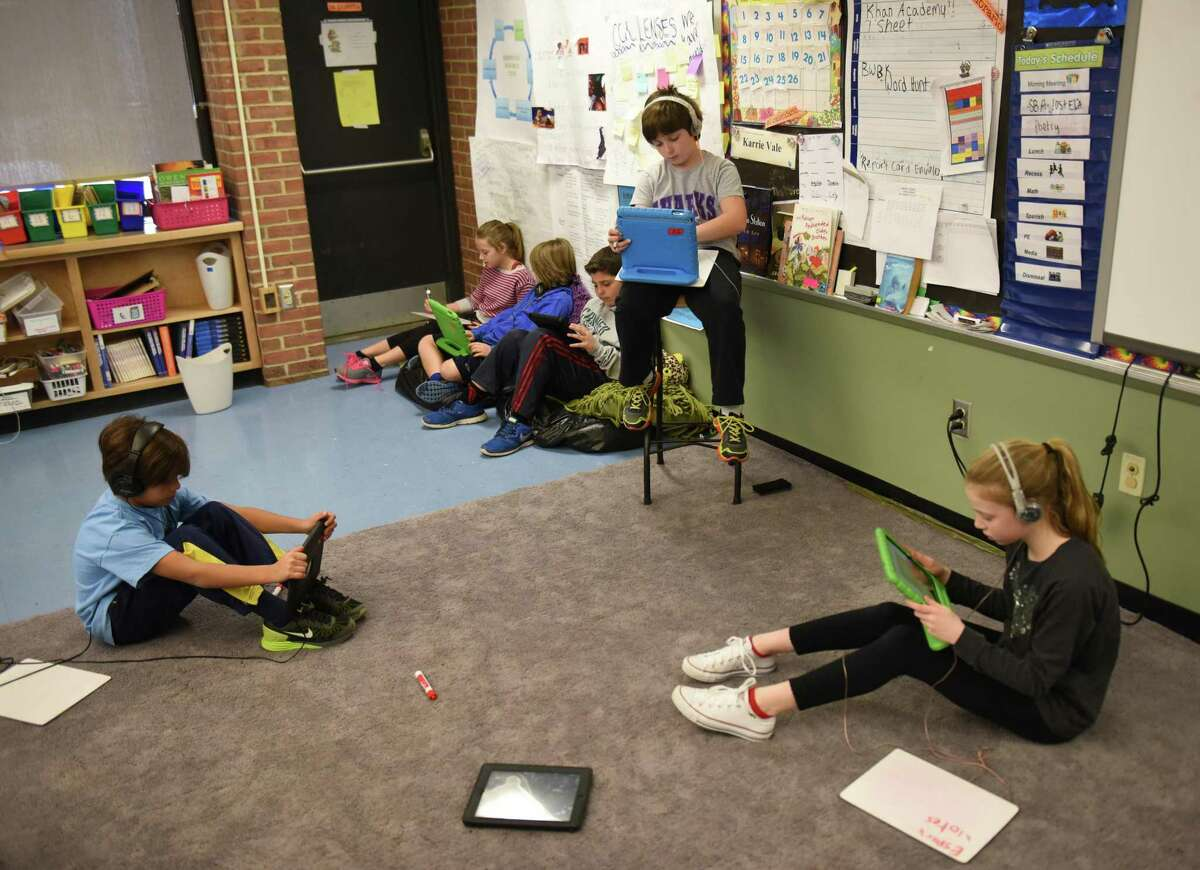 Tre Begasse, left, Daniela Pompa, right, and other fifth-graders use the eSpark iPad app at Parkway School in Greenwich, Conn. Thursday, March 26, 2015.