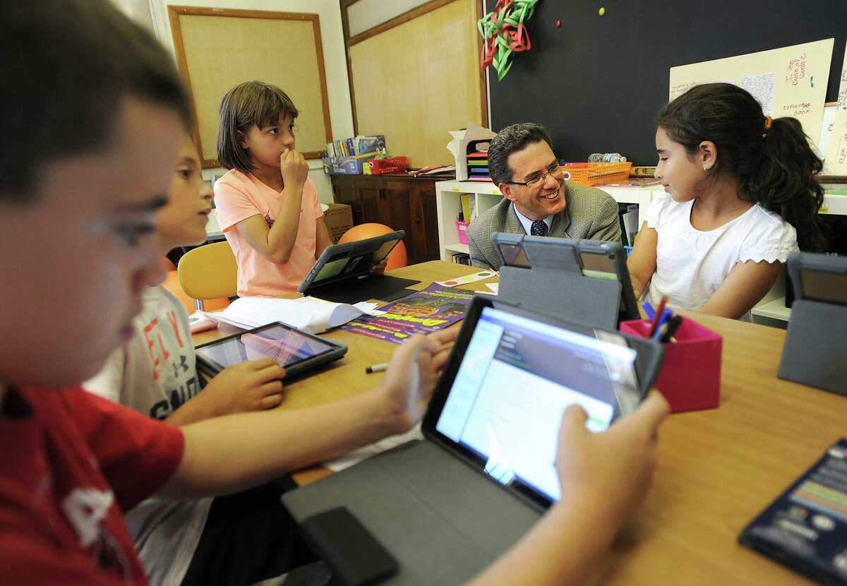 Bammy Award national finalist Principal Chris Weiss chats with student Sabrina Knoll, 9, as students work on iPads in their fifth grade classroom at Riverside School in Greenwich, Conn. on Thursday, September 24, 2015.