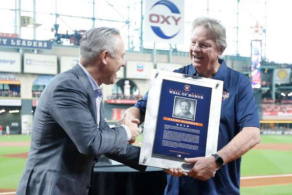 Former Houston Astros pitcher Larry Dierker shakes hands with Reid Ryan after being inducted into the Media Wall of Honor before an MLB baseball game at Minute Maid Park, Sunday, Sept. 22, 2019, in Houston.
