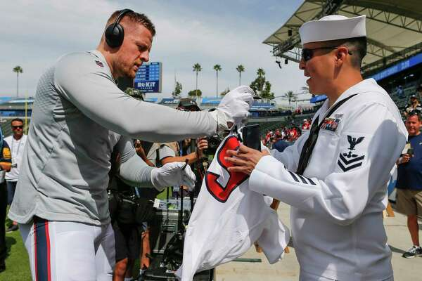 Houston Texans defensive end J.J. Watt, left, autographs a jersey for AO2 Eugenio Reyna, of Gonzalez, Texas, before and NFL game against the Los Angeles Chargers at Dignity Health Sports Park on Sunday, Sept. 22, 2019, in Carson, Calif.