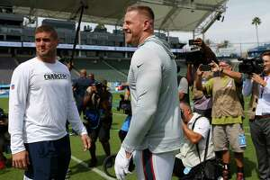 Los Angeles Chargers fullback Derek Watt, left, and his brother Houston Texans defensive end J.J. Watt talk on the field before an NFL football game at Dignity Health Sports Park on Sunday, Sept. 22, 2019, in Carson, Calif.