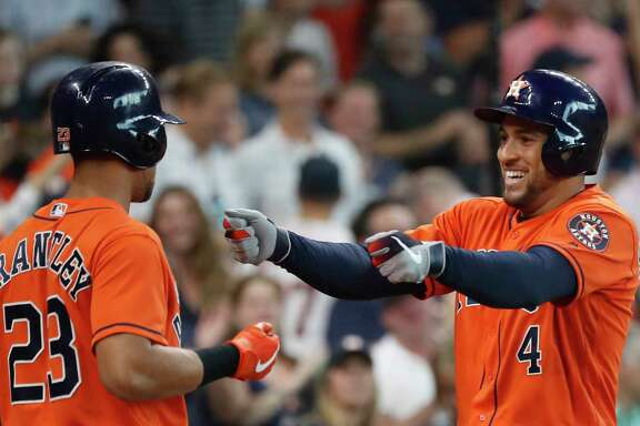 Houston Astros George Springer (4) hugs Michael Brantley (23) after hitting his third home run of the day in the fourth inning of an MLB baseball game at Minute Maid Park, Sunday, Sept. 22, 2019, in Houston.