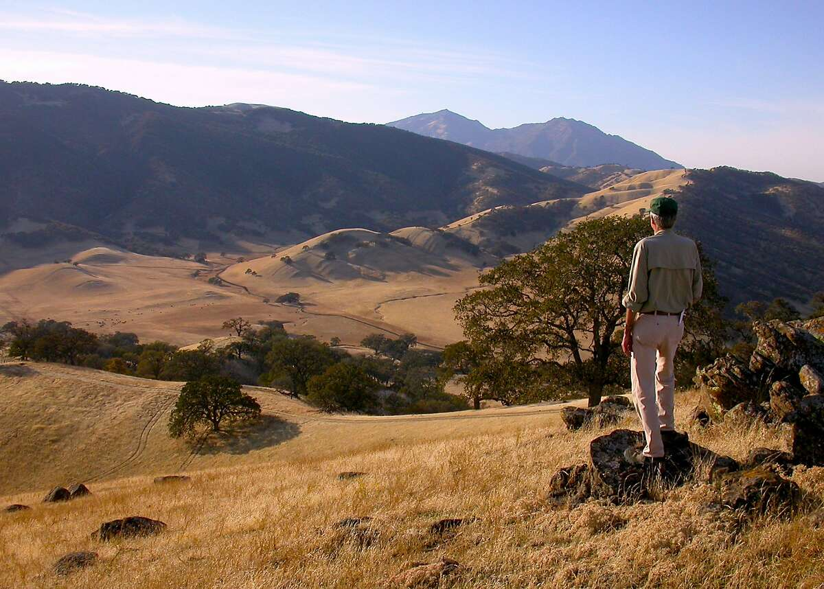 Ned MacKay, with more than 20,000 trail miles as a member of the East Bay Regional Parks Volunteer Safety Patrol, at one of his favorite rocks on the Hardy Canyon Trail for the view over Round Valley and to Mount Diablo