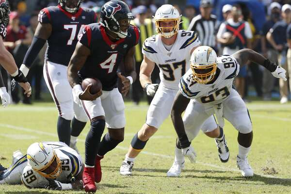 Houston Texans quarterback Deshaun Watson (4) steps out of the grasp of Los Angeles Chargers defensive tackle Jerry Tillery (99) as he scrambles out of the pocket during the second quarter of an NFL football game at Dignity Health Sports Park on Sunday, Sept. 22, 2019, in Carson, Calif.
