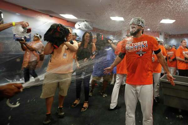 Houston Astros relief pitcher Roberto Osuna gets sprayed by champagne as the team celebrated the team's win and clinching the AL West crown in the clubhouse after an MLB baseball game at Minute Maid Park, Sunday, Sept. 22, 2019, in Houston.