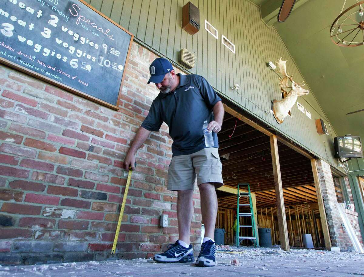 Vernon's Kuntry Katfish owner Buster Bowers measures how high the water got into his restaurant following Hurricane Harvey, Friday, Sept. 8, 2017, in Conroe. Bowers said the Conroe restaurant has received an outpouring of support from the community, including some 50 customers and employees who helped with demo after the establishment was flooded with three feet of water following Harvey.