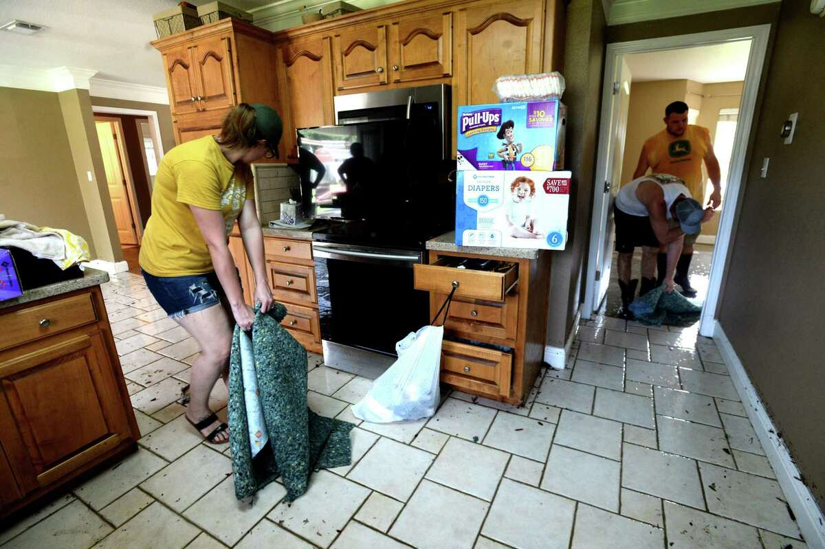 Hailey Pelton drags wet carpet from the home of Jarrad and Ashley McClelland as she and others help begin the process of recovery from Imelda's torrential rains and flooding Friday. Photo taken Friday, September 20, 2019 Kim Brent/The Enterprise