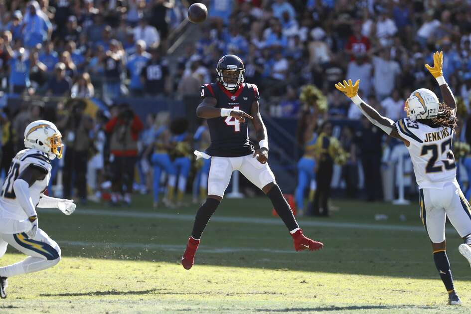 Houston Texans quarterback Deshaun Watson (4) throws a pass between Los Angeles Chargers defensive backs Desmond King (20) and Rayshawn Jenkins (23) to Texans tight end Jordan Akins (88) for a 56-yard touchdown pass during the fourth quarter of an NFL football game at Dignity Health Sports Park on Sunday, Sept. 22, 2019, in Carson, Calif.