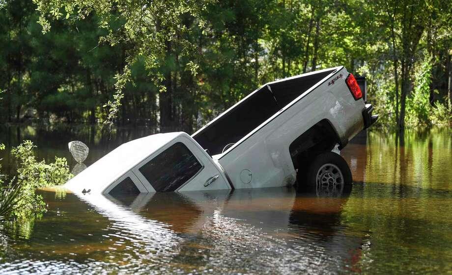 A truck lays halfway submerged off of flooded Texas 124 near Fannett Sunday. Photo taken on Sunday, 09/22/19. Ryan Welch/The Enterprise Photo: Ryan Welch, Beaumont Enterprise / The Enterprise / © 2019 Beaumont Enterprise