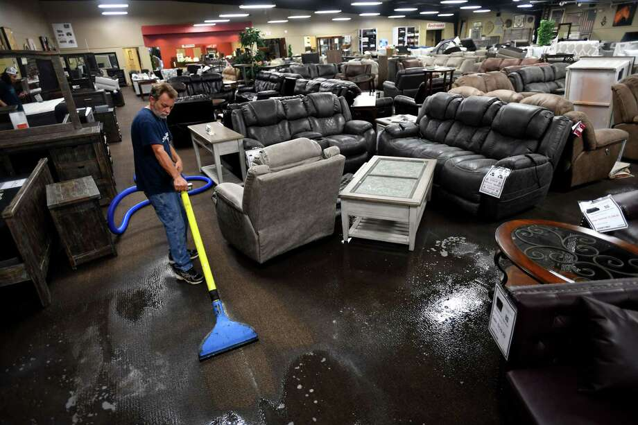 Joe Cantrell vacuums water from the carpet at Home Furniture in Beaumont on Saturday. The store was forced to replace its inventory after inches of water from Tropical Depression Imelda entered the building.   Photo taken Saturday, 9/21/19 Photo: Guiseppe Barranco/The Enterprise, Photo Editor / Guiseppe Barranco ©