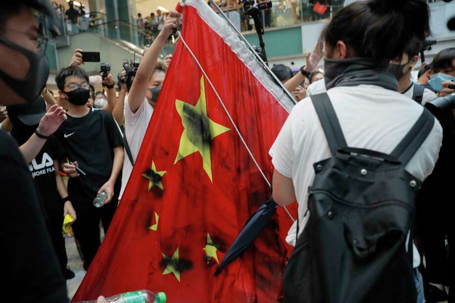 Protesters vandalize a Chinese national flag during a protest at a mall in Hong Kong on Sunday, Sept. 22, 2019. Hong Kong's pro-democracy protests, now in their fourth month, have often descended into violence late in the day and at night. A hardcore group of the protesters says the extreme actions are needed to get the government's attention. (AP Photo/Kin Cheung) Photo: Kin Cheung / Copyright 2019 The Associated Press. All rights reserved.