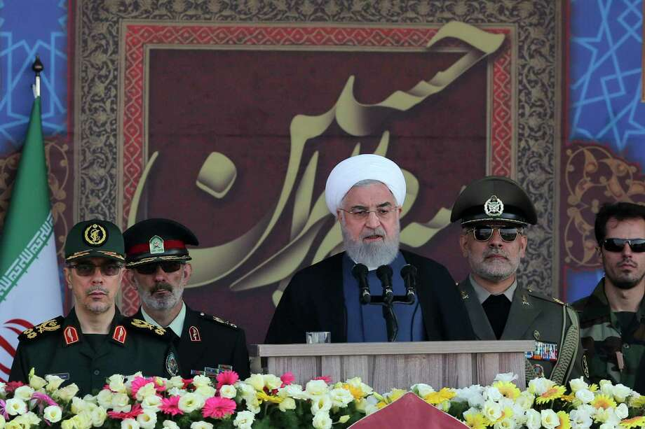In this photo released by the official website of the office of the Iranian Presidency, President Hassan Rouhani speaks at a military parade marking 39th anniversary of outset of Iran-Iraq war, in front of the shrine of the late revolutionary founder Ayatollah Khomeini, just outside Tehran, Iran, Sunday, Sept. 22, 2019. Chief of the General Staff of the Armed Forces Gen. Mohammad Hossein Bagheri stands at left. (Iranian Presidency Office via AP) / Office of the Iranian Presidency