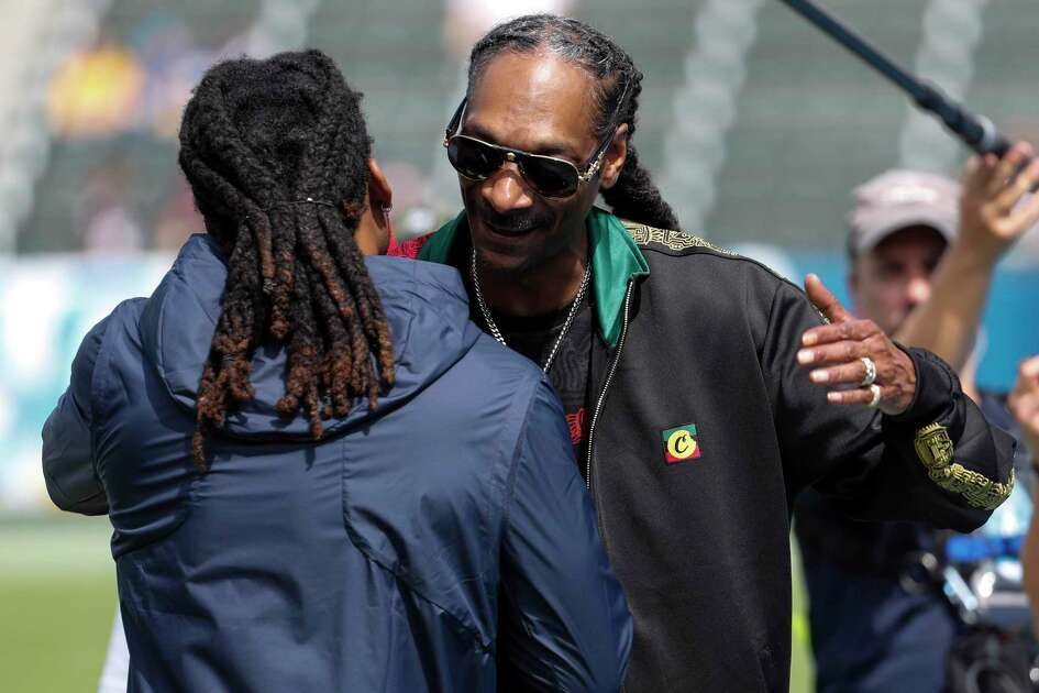 Recording artists Snoop Dogg embraces dHouston Texans cornerback Bradley Roby before an NFL football game against the Los Angeles Chargers at Dignity Health Sports Park on Sunday, Sept. 22, 2019, in Carson, Calif.