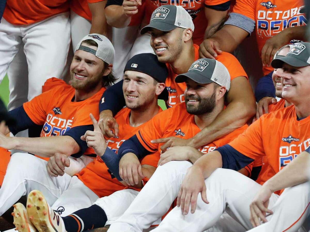 Josh Reddick, from left, Alex Bregman, Carlos Correa, Jose Altuve and manager A.J. Hinch bask in the Astros' third consecutive division championship, a feat last achieved by the club in 1997-99.
