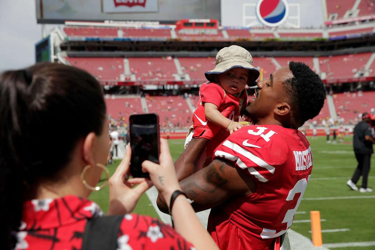 Raheem Mostert (31) kisses his son, Gunnar Mostert as his wife, Devon Mostert, left, takes a picture before the San Francisco 49ers played the Pittsburgh Steelers at Levi's Stadium in Santa Clara, Calif., on Sunday, September 22, 2019.