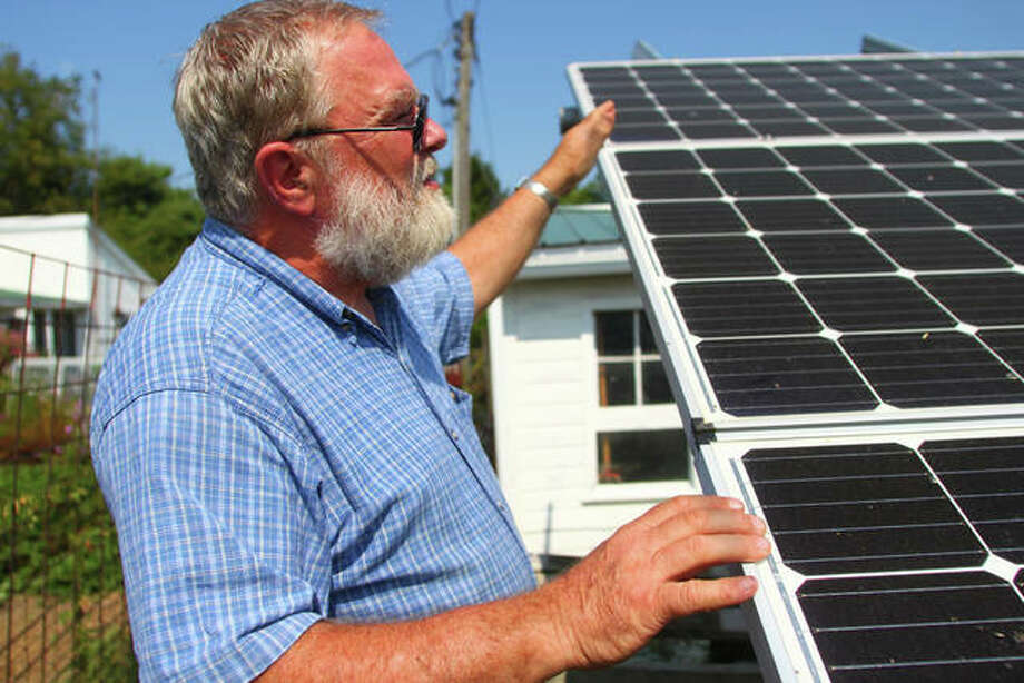 Ed Anderson describes the positioning of solar panels he and his wife had installed on their property two years ago. Photo: Rosalind Essig | Journal-Courier