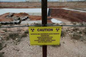 A caution sign surrounding the low-level radioactive waste site at Waste Control Specialists (WCS) near Andrews, Texas. WCS provides services to store low-level nuclear waste and is in the process of applying for a license to be an interim storage facility for high-level radioactive waste.