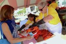 Volunteer Amy Schroeder-Reggio of Westport serves the first lobster of the day to Karen Jones of Westport at the 8th annual Lobster Fest at Compo Beach on Saturday, Sept. 21, 2019, in Westport, Conn.