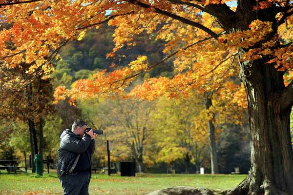 "Dennis Mitchell of Sydney, Australia, stopped at Squantz Pond in New Fairfield Monday, Oct. 24, 2016, to photograph the fall foliage around the state park. Mitchell is on the last leg of a six-week fall foliage tour which began in Boston, went through Maine, New Hampshire and Vermont and now Connecticut. He says Sydney has ""pockets"" of fall colors but "" nothing on the scale of New England."""